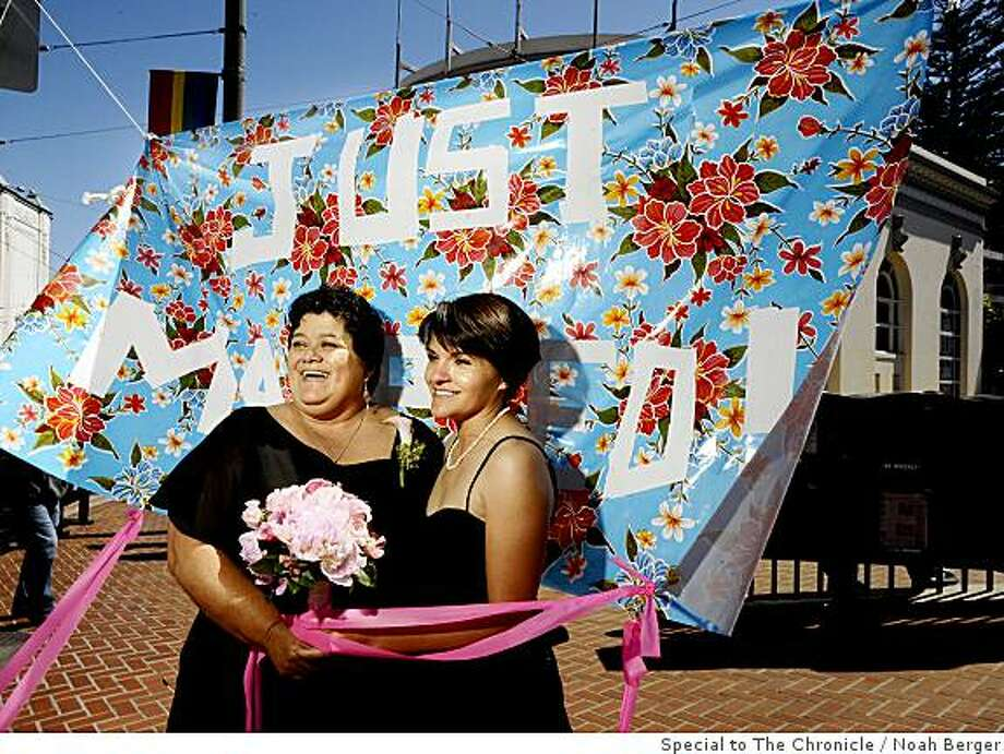 Luz Salcedo, right, and Karen Fernandez commemorate their marriage on Castro St. The couple, who live in San Leandro and were married in Oakland this morning, traveled to the Castro district to celebrate. Photo by Noah Berger / Special to the Chronicle Photo: Noah Berger, Special To The Chronicle