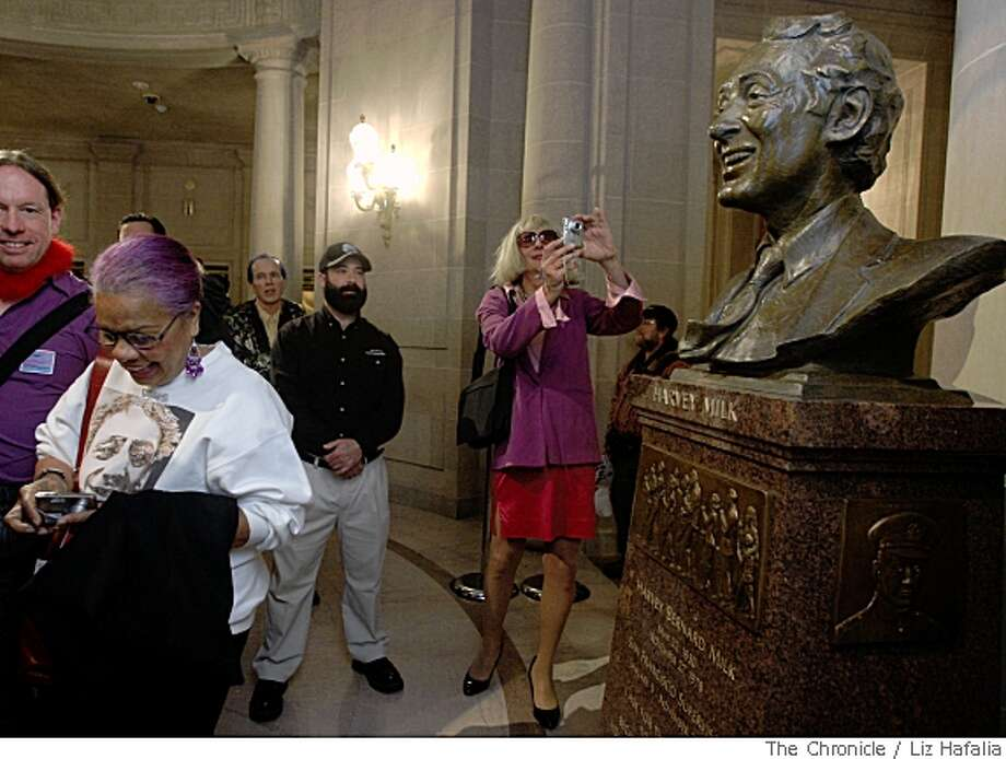 Lucrecia Fontes (left) looks at her pictures of Harvey Milk's bust after it's unveiling at City Hall in San Francisco, Calif., on Thursday, May 22, 2008.Photo by Liz Hafalia / The Chronicle Photo: Liz Hafalia, Chronicle