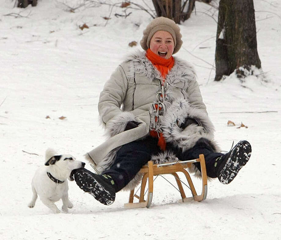 A woman enjoys a sled ride with her dog at Lietzensee park on January 6, 2010 in Berlin, Germany. Subzero temperatures are gripping Germany and are predicted to fall even further later in the week. Photo: Andreas Rentz, Getty Images