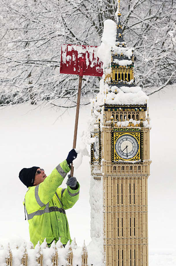 Legoland employee, Graeme Williams clears snow from a model building representing the London landmark Big Ben in Windsor, Berkshire on January 6, 2010. Britain braced for more transport chaos Wednesday as heavy snow and freezing temperatures swept south,one day after gripping northern England and Scotland. Blizzards hit northern parts of Britain on Tuesday, halting transport and major football fixtures, as well as closing airports and hundreds of schools. Photo: Carl De Souza, AFP / Getty Images