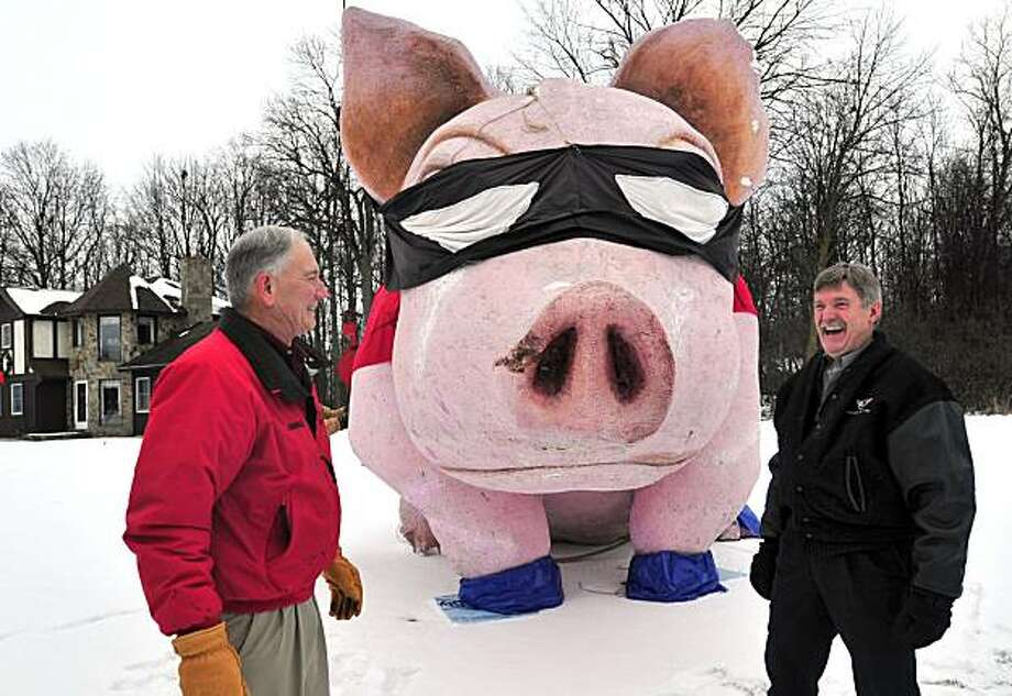 In this Jan. 5, 2010 photo, Saginaw County Commissioner Dennis Krafft, right, laughs at the huge Styrofoam pig his friend, Al Weiss, left, placed in his yard in Frankenmuth, Mich. Weiss, who won use of the pig while bidding at a charity event, placed thepig there as a surprise for Krafft's 60th birthday. Photo: Jeff Schrier, AP