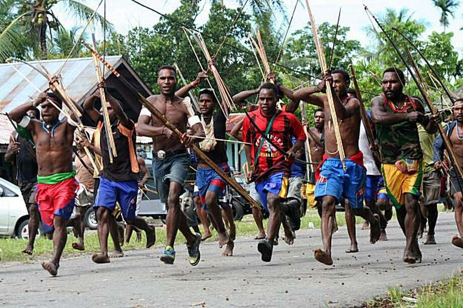 Amungme tribe men run to strike another group of Amungme as a dispute has arisen in Timika on January 5, 2010.  The Amungme tribe is one of around 312 different tribes in Papua who commonly end their disputes in traditional fashion. There is about 13,000 Amungme living in the highlands of the Papua province of Indonesia where the Grasberg mine owned by Freeport-McMoRan is situated. Photo: Tjahjo Eranius, AFP / Getty Images