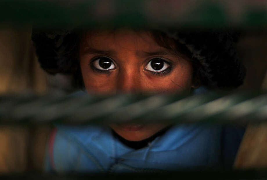 A Pakistani girl looks on as she lines up with other women to get a ration of rice during a donated food distribution in Islamabad, Pakistan, Wednesday, Jan. 6, 2010. Photo: Muhammed Muheisen, AP
