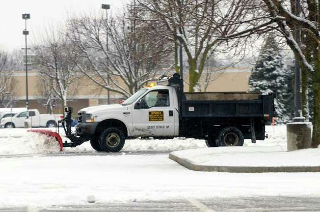 A plow truck operator clears snow from the parking lot at the Kmart on Thursday, Jan. 12, 2012 in Clifton Park, N.Y.  (Paul Buckowski / Times Union) Photo: Paul Buckowski