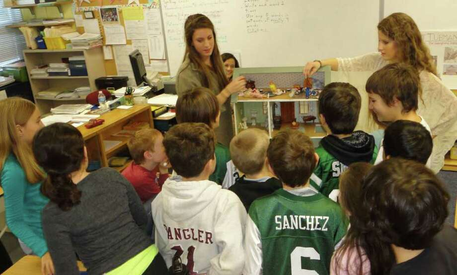 Students in teacher Rich Curesky's classroom at Jennings School gather around two Fairfield Warde High School students Friday to learn about Harriet Tubman, slavery and the Underground Railroad. Victoria Edison, left, and classmate Eva Filan, both 16, showed the young students a model of a safe house that might be found on the Underground Railroad and answered questions about that time period in American history. Photo: Meg Barone / Fairfield Citizen freelance