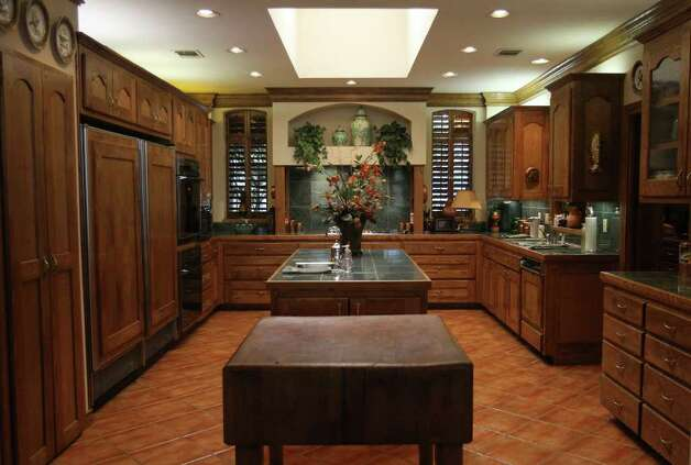 The kitchen in the Elm Creek home of Joe and Bettye Maurin features a large butcher block (center) and carries the wood paneling theme in the home on appliances like the refridgerator on the left. (Tuesday January 10, 2012) JOHN DAVENPORT/jdavenport@express-news.net Photo: JOHN DAVENPORT, SAN ANTONIO EXPRESS-NEWS / SAN ANTONIO EXPRESS-NEWS (Photo can be sold to the public)