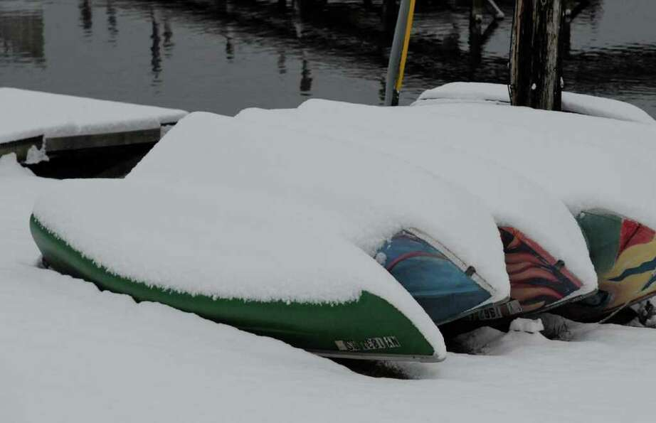 Snow covers some of the boats used for rentals in better weather on the north shore of Saratoga Lake
