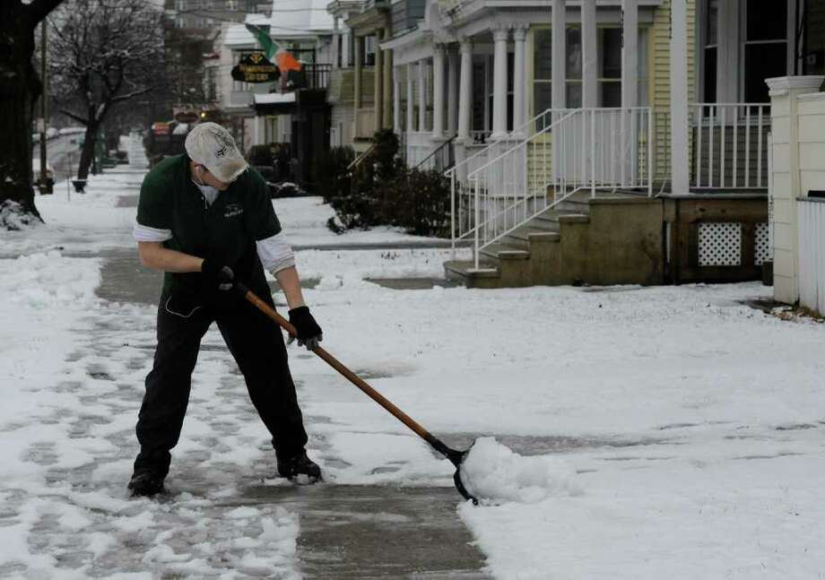 Jamie Sarinelli of Albany Nursery does some shoveling for one of his clients on a snowy day on Western Avenue in Albany, N.Y. Jan, 11, 2012.  (Skip Dickstein / Times Union) Photo: SKIP DICKSTEIN / 2012