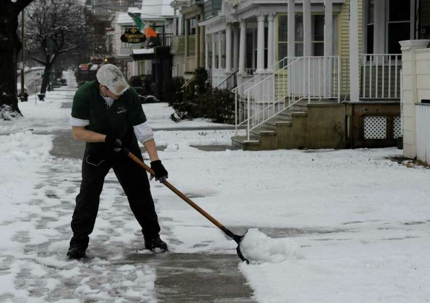 Jamie Sarinelli of Albany Nursery does some shoveling for one of his clients on a snowy day on Weste