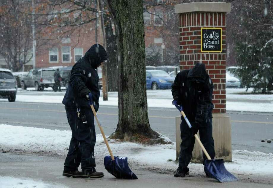 St. Rose College workers Anthony Brea, left and Fernando Tejada clear slush from the sidewalks near the intersection of Partridge Street and Western Avenue in Albany, N.Y. Jan, 11, 2012.  (Skip Dickstein / Times Union) Photo: SKIP DICKSTEIN / 2012