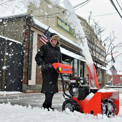 Shop owner Michael Bernstein clears snow from the sidewalk in front of Simon's Mens Wear in Niskayuna Thursday Jan. 12, 2012.    (John Carl D'Annibale / Times Union) Photo: John Carl D'Annibale / 10016078A