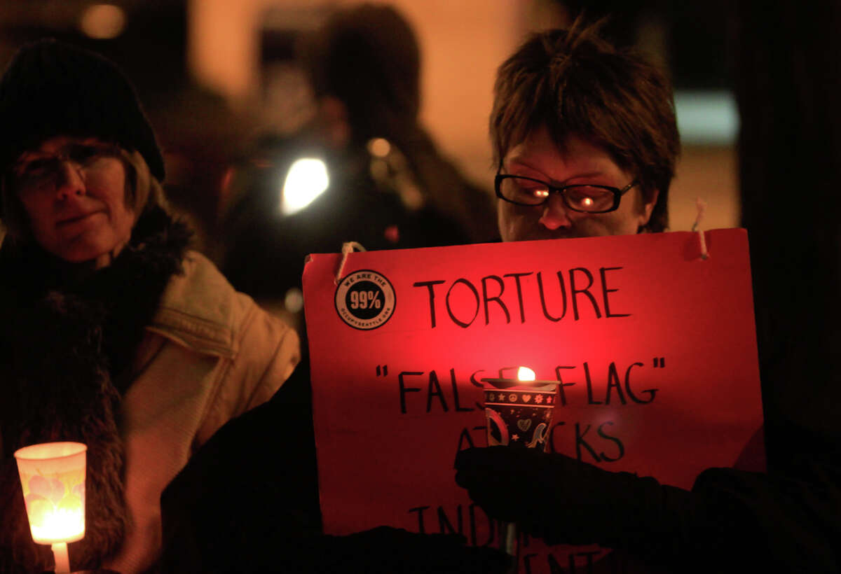 Deborah Scott holds a sign while protesting the continuing use of the Guantanamo Bay detention camp to detain prisoners without trial. About 30 activists gathered in front of the Federal building in downtown Seattle on Wednesday, Jan. 11,2012, the 10th anniversary of the Guantanamo Bay facility beginning operation as an extrajudicial detainment and facility.