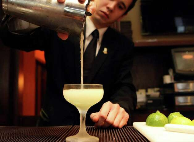 TASTE: Jake Corney prepares a Ivy Gimlet on Friday Jan. 6, 2012. Bohanan's has organized the San Antonio Cocktail Conference, the first of its kind for Texas. It's modeled after the Manhattan Cocktail Conference. Please shoot photos of bartenders mixing cocktails, the tools and ingredients they use, such as shakers, large format ice, etc.  HELEN L. MONTOYA/hmontoya@express-news.net Photo: HELEN L. MONTOYA, San Antonio Express-News / SAN ANTONIO EXPRESS-NEWS