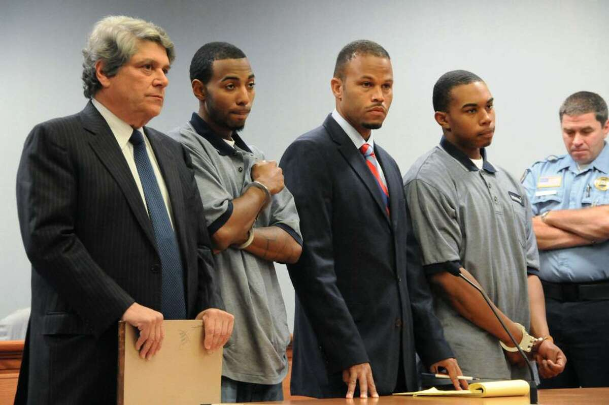 Prior to being individually arraigned, John William Lomax III, right, accompanied by his attorney Deron Freeman, second right, and Hakim Muhammad, with his attorney Gerald Klein, far left, appear for their arraignment before a Superior Court judge with regard to charges connected with the slaying of UConn football player Jasper Howard, in a courtroom at Rockville Superior Court, in Rockville, Conn., on Wednesday, Oct. 28, 2009. (AP Photo/George Ruhe)