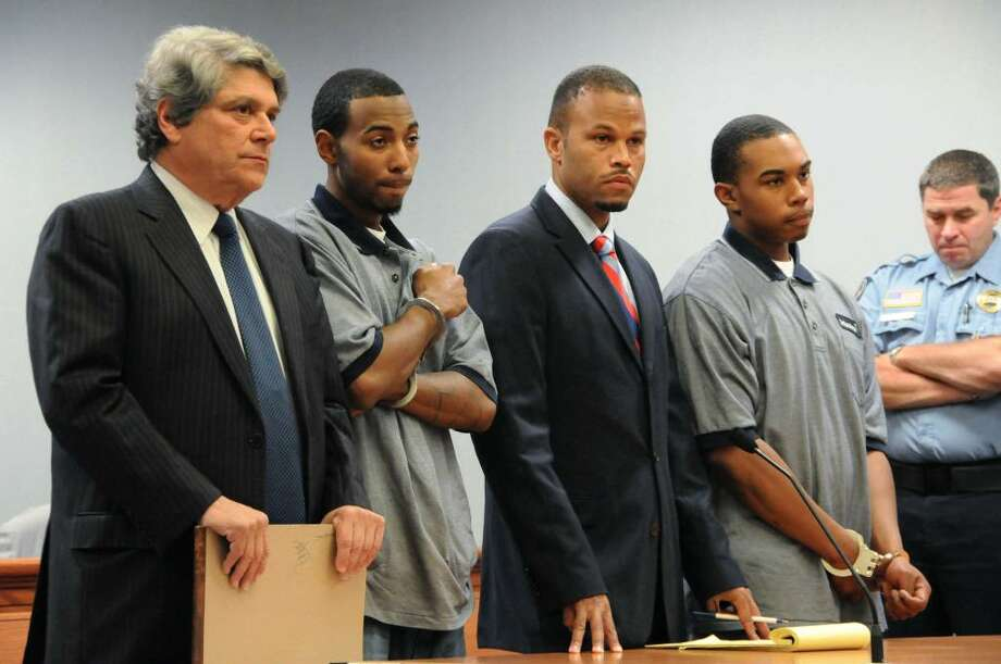 Prior to being individually arraigned,  John William Lomax III, right, accompanied by his attorney Deron Freeman, second right,  and Hakim Muhammad, with his attorney Gerald Klein, far left,  appear for their arraignment before a Superior Court judge with regard to charges connected with the slaying of UConn football player Jasper Howard, in a courtroom at Rockville Superior Court, in Rockville, Conn., on Wednesday, Oct. 28, 2009. (AP Photo/George Ruhe) Photo: George Ruhe, AP / FR92389 AP