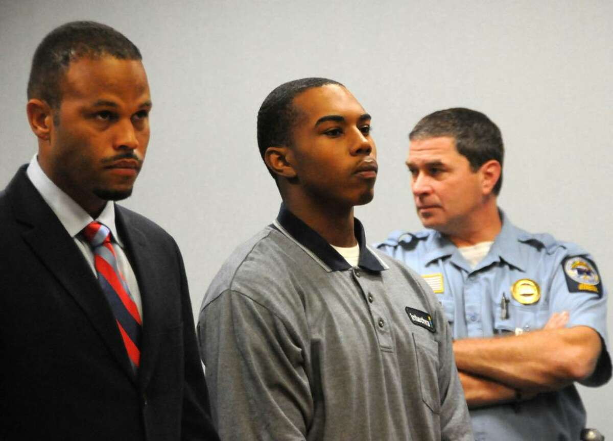 John William Lomax III, center, accompanied by Attorney Deron Freeman, left, is arraigned on charges connected with the slaying of UConn football star Jasper Howard, in a courtroom at Rockville Superior Court, in Rockville, Conn., on Wednesday, Oct. 28, 2009. (AP Photo/George Ruhe)