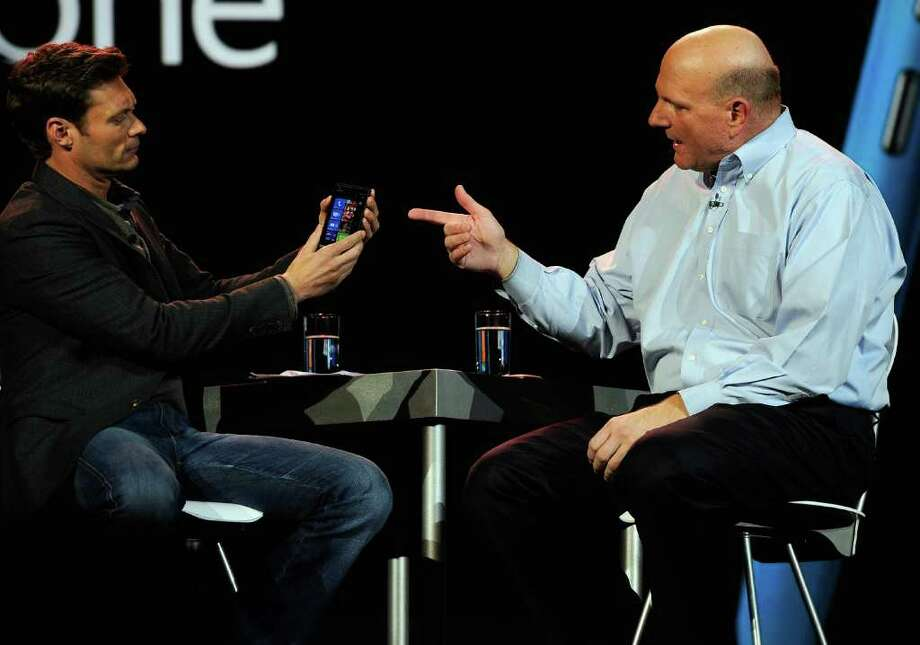 Nokia hitched its hopes of revival to Windows Phone. Here, Microsoft CEO Steve Ballmer (left) shows the new Nokia Lumia 900 phone to host Ryan Seacrest as he delivers a keynote address at the 2012 International Consumer Electronics Show at the Las Vegas Convention Center on Jan. 9, 2012. Photo: Kevork Djansezian, Getty Images / 2012 Getty Images