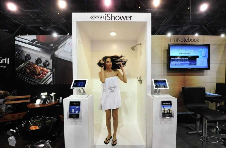 The 2012 International Consumer Electronics Show, in Las Vegas, features the latest in more-than-just-smart phones, humongous 3D televisions, robots, high-tech bottle openers and more gadgets you don't really need but can't live without. The show features a record 3,100 companies from around the world displaying their goods over a space equivalent to more than 35 football fields and ends Friday. Here, a model appears to step out of the shower at the iShower booth, which features an easily detachable Bluetooth enabled shower speaker, on January 10, 2012. Photo: FREDERIC J. BROWN, AFP/Getty Images / 2012 AFP