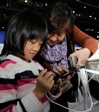 Andrea Jia, 8, and her mother, Lotus Chen, of California use the Galaxy Note smartphone with integrated S Pen at the Samsung booth at the 2012 International Consumer Electronics Show at the Las Vegas Convention Center January 10, 2012 in Las Vegas, Nevada. The Note utilizes the first HD screen for an AT&T phone. It runs on Android 2.3, is capable of 1080p video recording, has an 8-megapixel autofocusing rear facing camera and a 2-megapixel front facing camera. Photo: Ethan Miller, Getty Images / 2012 Getty Images