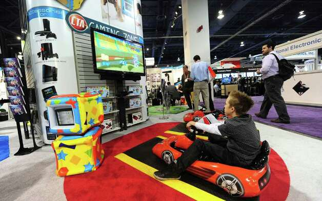 A child plays a game from an inflatable sports car at the display booth of CTA at the International Consumer Electronics Show in Las Vegas, Nevada, on January 11, 2012.  Photo: FREDERIC J. BROWN, AFP/Getty Images / 2012 AFP
