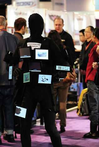 Accesory Power Tablet Man (left) roams the hall between booths at the International Consumer Electronics Show in Las Vegas, Nevada, on January 11, 2012. Photo: FREDERIC J. BROWN, AFP/Getty Images / 2012 AFP
