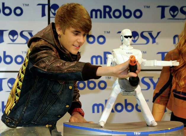Singer Justin Bieber holds a microphone in front of the mRobo Ultra Bass as he unveils the portable speaker and dancing robot at the TOSY Robotics booth at the 2012 International Consumer Electronics Show at the Las Vegas Convention Center January 11, 2012 in Las Vegas, Nevada. Photo: Ethan Miller, Getty Images / 2012 Getty Images