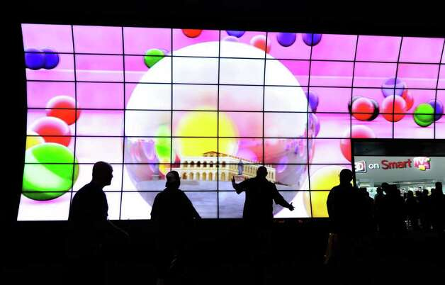 Attendees walk by an LG Cinema 3-D Smart TV display at the LG Electronics booth at the 2012 International Consumer Electronics Show at the Las Vegas Convention Center January 11, 2012 in Las Vegas, Nevada. Photo: Ethan Miller, Getty Images / 2012 Getty Images