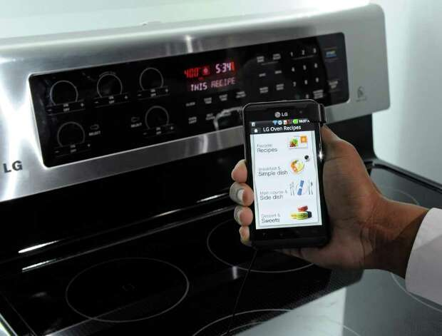 A smartphone sends instructions to an oven using LG's newest Smart ThinQ technology at the LG Electronics booth at the 2012 International Consumer Electronics Show at the Las Vegas Convention Center January 11, 2012 in Las Vegas, Nevada. LG's line of smart home appliances coming out in 2012, have improved connectivity between them and other devices like phones and TVs, allowing for easier control and monitoring of the devices.  Photo: Ethan Miller, Getty Images / 2012 Getty Images