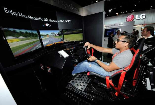 "Sujhon Das of Nevada plays the ""Need for Speed: Shift"" racing video game using a racing motion machine and LG Cinema 3D IPS TVs at the LG Electronics booth at the 2012 International Consumer Electronics Show at the Las Vegas Convention Center January 11, 2012 in Las Vegas, Nevada. Photo: Ethan Miller, Getty Images / 2012 Getty Images"