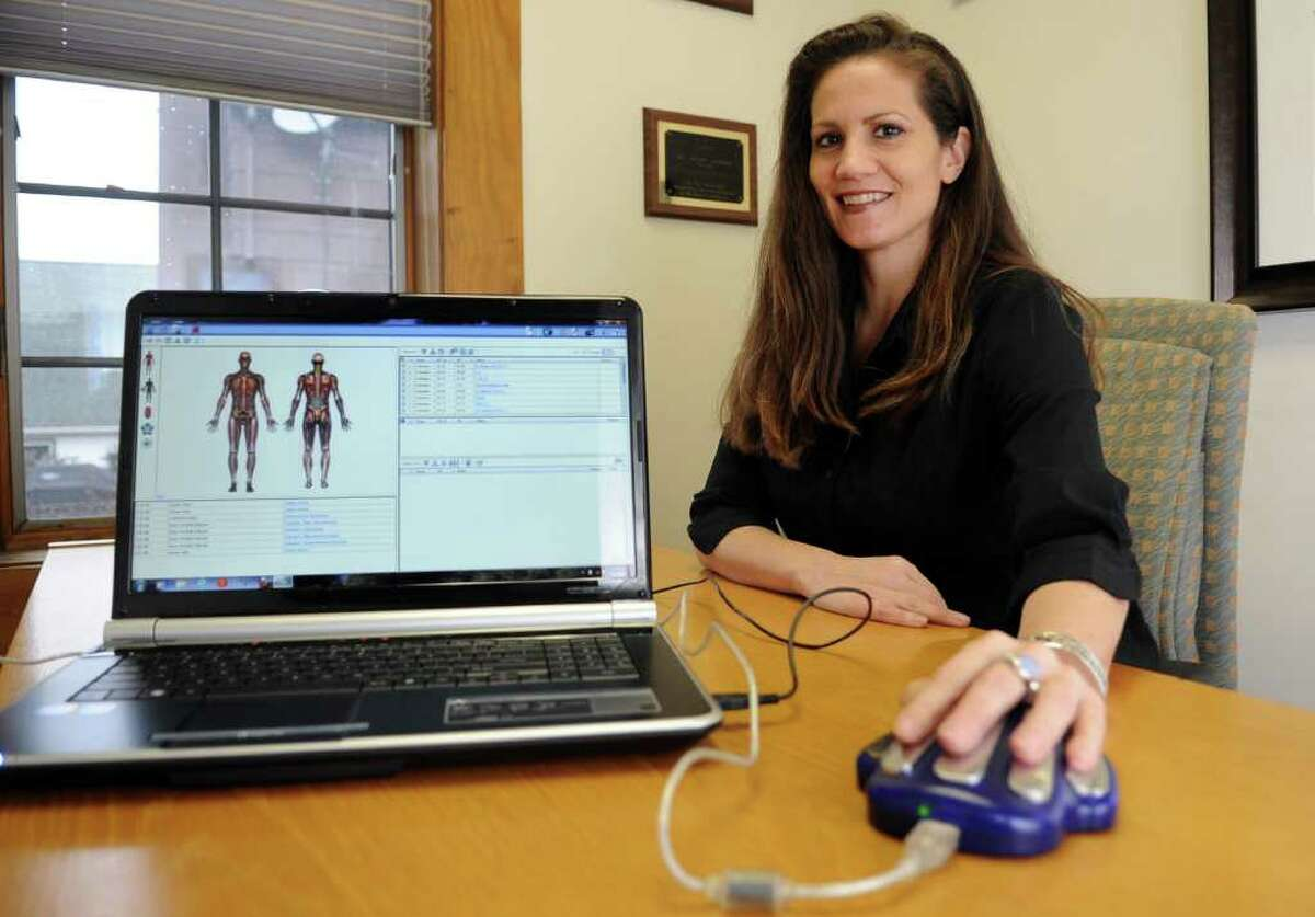 Jennifer Hanley, owner of JH Wellness, poses for a photo in her office in Stamford on Thursday, January 12, 2012. Hanley uses a hand cradle attached to special software in her computer to scan energy and meridians in the hand to detect areas of the body which need attention.
