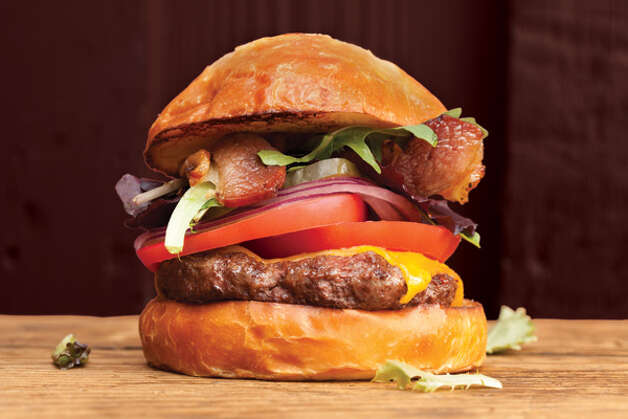 Best Beefy Burgers: The most epic bacon cheeseburger: The Swinery Burger with Bacon, at West Seattle's The Swinery, $9. Grilled over charcoal outside in the bare-bones Swinery courtyard, the Swinery burger is a true thing of beauty: one-third pound of house-ground Painted Hills beef with soft onions, house-cured Swinery bacon cooked until softly crisp, your choice of cheese, lettuce, tomatoes and house-made pickles on a soft, sweet brioche bun from Macrina Bakery. To see more of Seattle Magazine's picks for Seattle's Best Beefy Burgers, click here for the list. Credit: Hayley Young