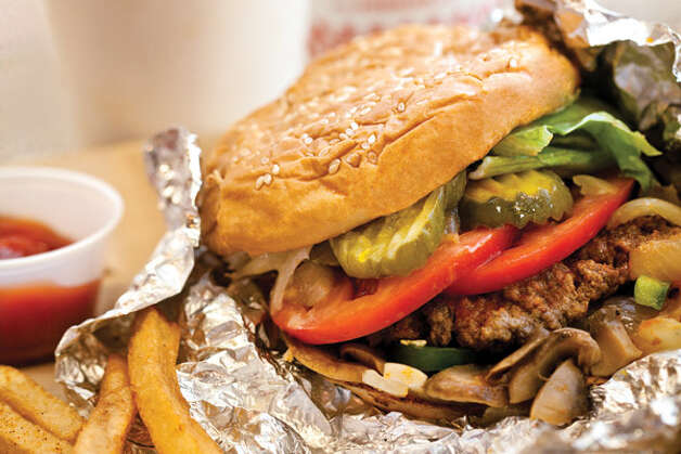 Best Burgers Under $5: Sure, it's a national chain, but at clean, bright and friendly Five Guys (in Renton, Northgate and Redmond), you'll find what is easily one of the best burgers around for $5. The best part: All the toppings—grilled onions and mushrooms, pickles, lettuce, tomatoes, green peppers, jalapeños, relish and more—are free. To see more of Seattle Magazine's picks for the Best Burgers under $5, click here for the list. Credit: Rina Jordan