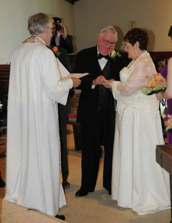 Bridegroom Bruce A. Agnew, center, places a wedding ring on the finger of the bride, Joan Simons Constantikes, right. The couple  wed on Oct. 22. Photo: Contributed Photo