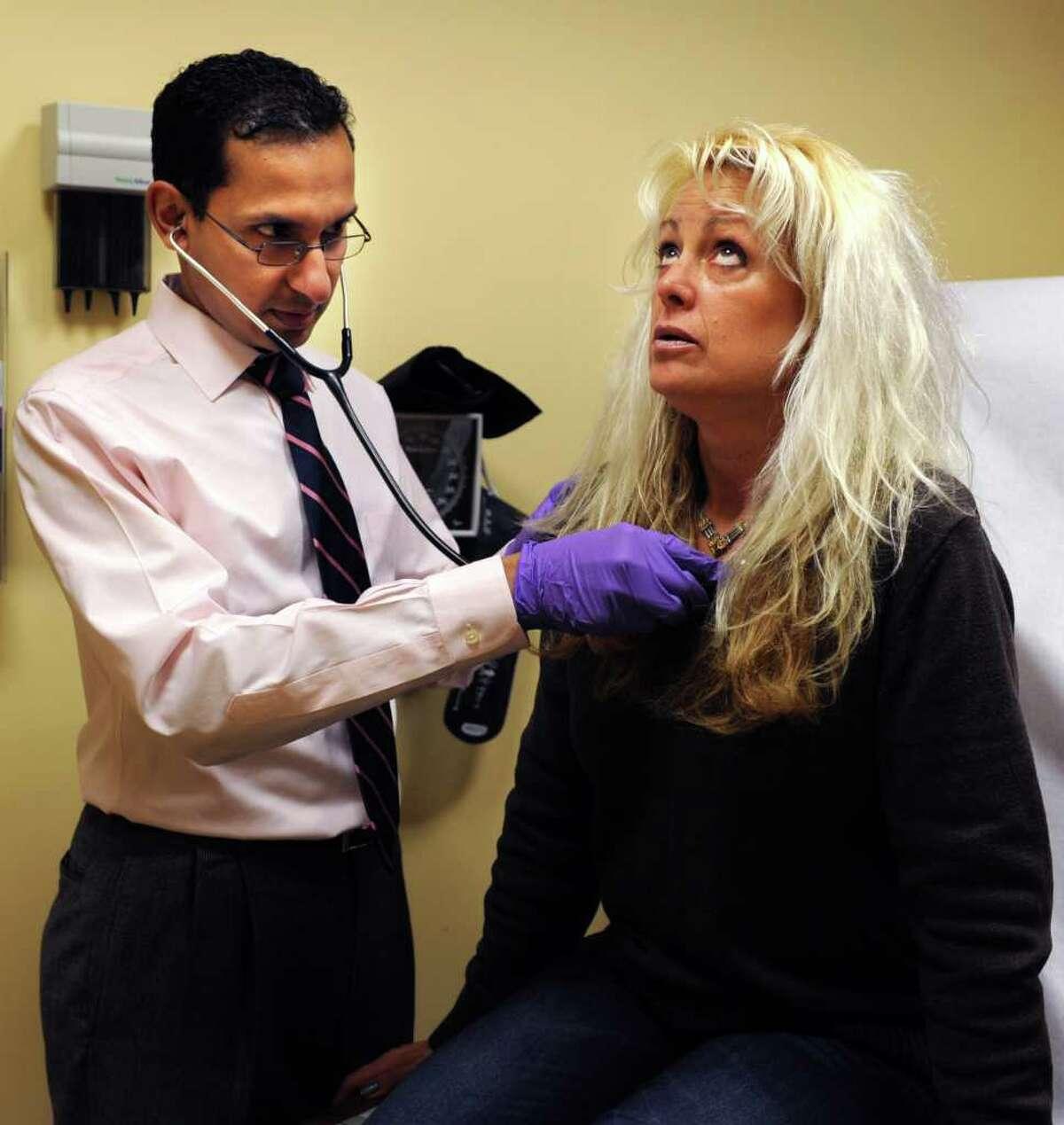 Dr. Sanjeev Rao examines Marcia Barry, of Fairfield, Thursday, Jan. 12, 2012 at the Fairfield Urgent Care Clinic on Stillson Road in Fairfield, Conn.