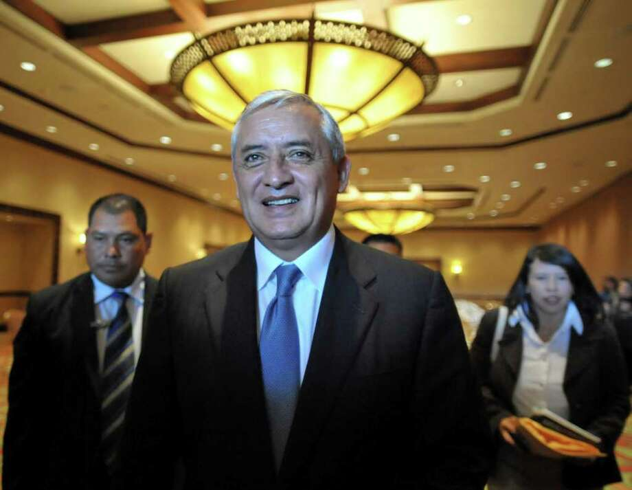 Guatemalan President-elect Otto Perez Molina smiles with journalists after holding a meeting with deputies of his party in Guatemala City, on January 12, 2012. Retired general Perez Molina is to succeed President Alvaro Colom when he takes office on January 14.  AFP PHOTO/Johan ORDONEZ Photo: JOHAN ORDONEZ, AFP/Getty Images / 2012 AFP
