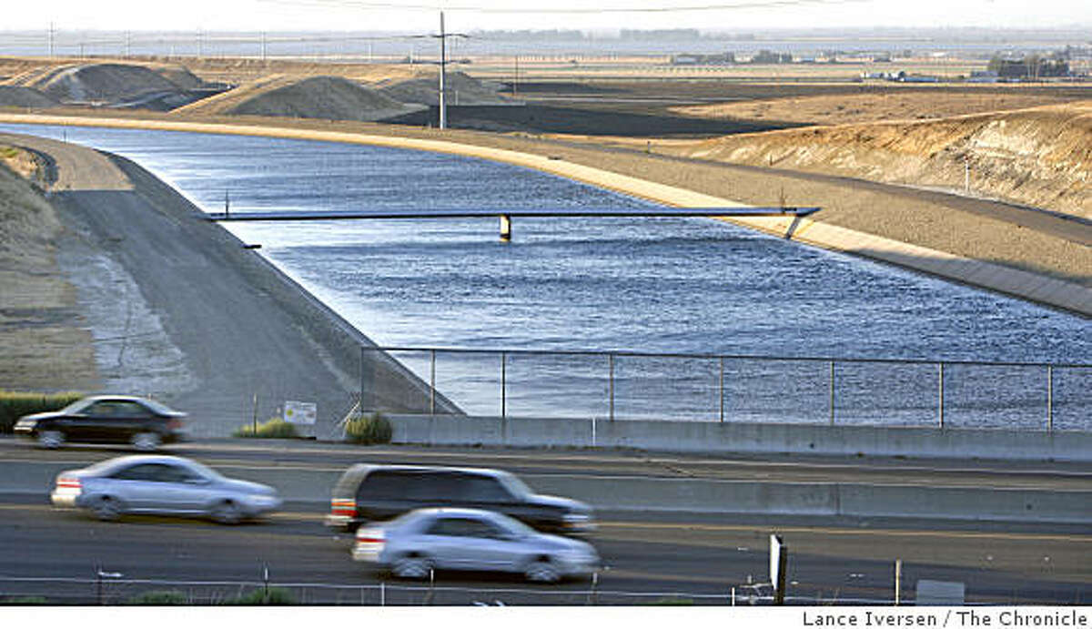 Delta water heading south passes under commuters heading east on 580 outside of Tracy.