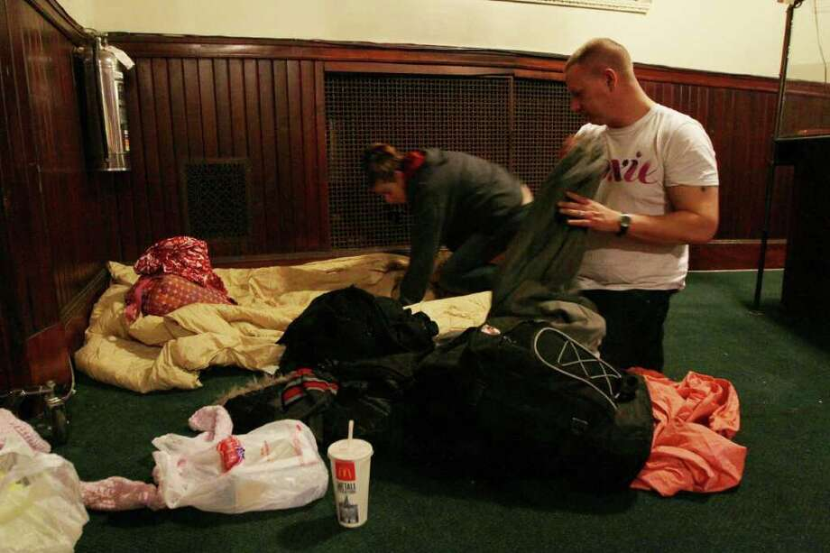HOLD FOR STORY BY MEGHAN BARR - Chris Allen, right, and his wife Caroline Allen set up bedding as they prepare to spend the night Wednesday Jan. 11, 2012 in a church space being funded by Occupy Wall Street for Occupy Wall Street protestors at the West Park Presbyterian Church in New York.  The couple are from Port Jefferson, New York. The refugees from Manhattan?s Zuccotti Park had found their way to the cavernous Presbyterian church, hoping to stay for a few nights, maybe longer.  (AP Photo/Tina Fineberg) Photo: Tina Fineberg / FR73987 AP