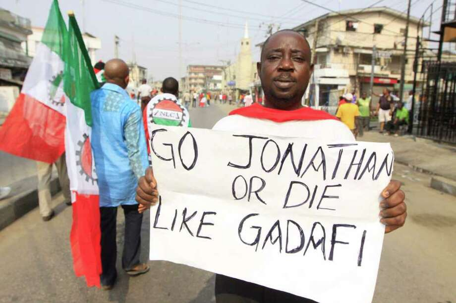 An man protest with a placard saying ' President Jonathan should go or die like Gadafi' on the removal of a fuel subsidy by the government in Lagos, Nigeria, Thursday, Jan. 12, 2012. A union representing 20,000 oil and gas workers in Nigeria threatened Thursday it would shut down all production starting Sunday to take part in the crippling nationwide strike over spiraling fuel prices. (AP Photo/Sunday Alamba) Photo: Sunday Alamba / AP