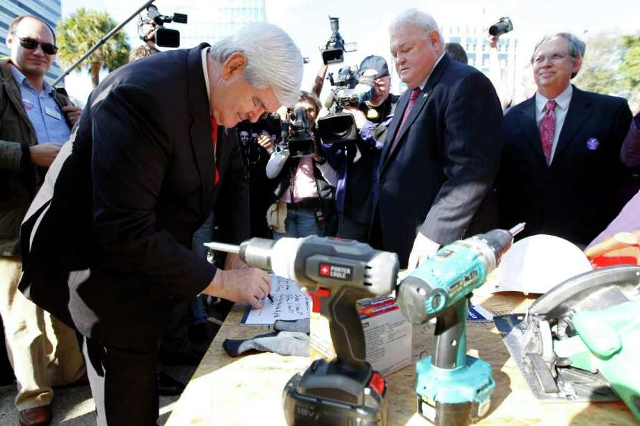 Republican presidential candidate Newt Gingrich signs a pledge in support of a home owner mortgage tax deduction, Thursday in Columbia, S.C. Photo: Matt Rourke / AP