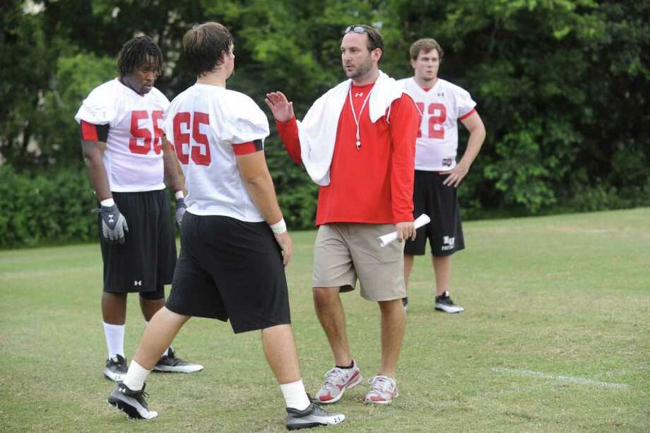 Lamar offensive line coach Nathan Reeves, center, works with Cardinal offensive linemen, from left,  Ryan Jones, Kameron Edwards, and Patrick Carlton during Lamar University's first football practice.  Thursday, August 5, 2010. Valentino Mauricio/The Enterprise Photo: Valentino Mauricio / Beaumont