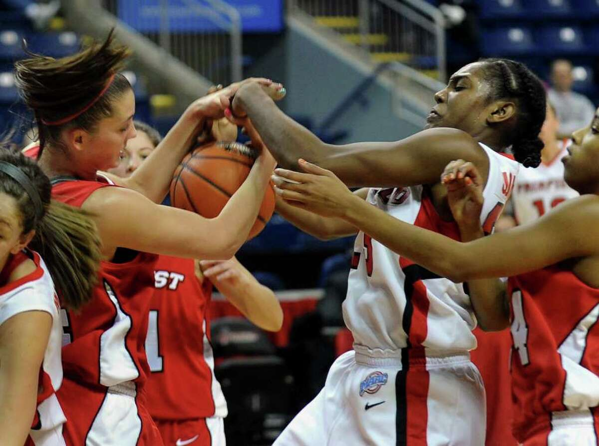 Fairfield University's #23 Taryn Johnson, and Marist's #34 Brandy Gang, left, grapple for a rebound, during womens basketball action at the Webster bank Arena in Bridgeport, Conn. on Thursday January 12, 2012.