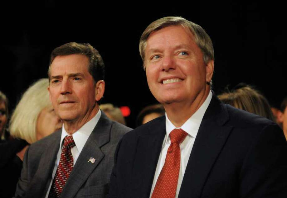 FILE - In this Nov. 12, 2011, file photo, Sen. Lindsey Graham, right, and Sen. Jim DeMint prepare to watch the CBS News/National Journal foreign policy debate at the Benjamin Johnson Arena in Spartanburg, S.C. In the 2012 Republican nominating contest, DeMint is like the pretty girl all the boys want to take to the prom. Nearly every GOP presidential candidate has come a-courting the South Carolina Republican ahead of his state?s Jan. 21 primary. (AP Photo/Richard Shiro, File) Photo: RICHARD SHIRO / FR159523 AP
