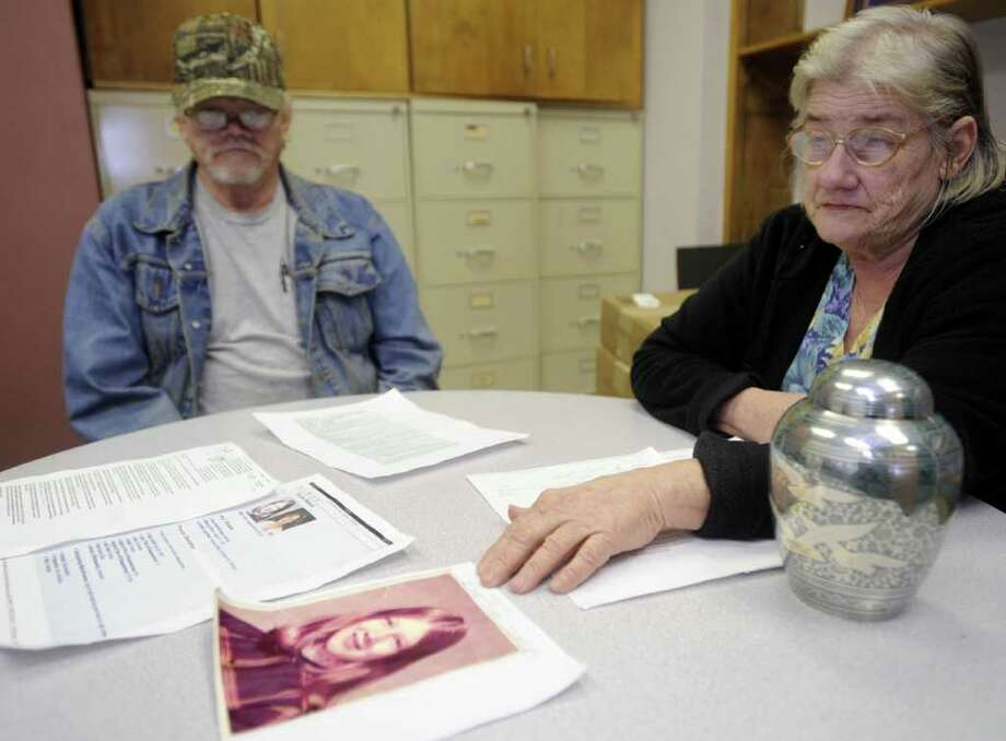 In this photo taken Jan. 10, 2012, Betty Wisecup, shows a photo of her daughter Ima Jean Sanders as Gary Wisecup, left, looks on, in Beaumont, Texas. The Wisecups learned late last year that skeletal remains found in Georgia were those of Betty's daughter Ima Jean Sanders, who went missing in 1974. Investigators believe the girl, who was 13 at the time, was killed by serial killer Paul John Knowles. Sander's ashes, which Wisecup had just received, are in the urn at right . Photo: AP
