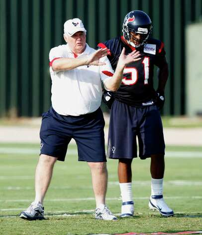 Defensive coordinator Wade Phillips of the Houston Texans goes over plays with inside linebacker Darryl Sharpton #51 during practice on the first day of training camp at Reliant Park on August 1, 2011 in Houston, Texas. Photo: Bob Levey, Getty Images / 2011 Getty Images
