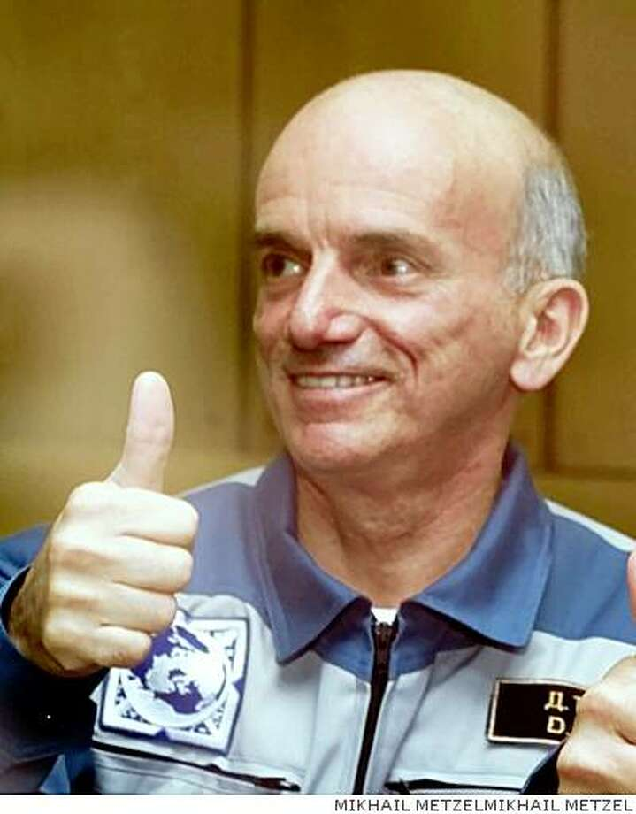Dennis Tito, a U.S. space tourist, gives a thumbs-up from behind a glass screen, designed to protect the cosmonauts from any last minute infections, in Baikonur, Kazakstan, Friday April 27, 2001, on the eve of his scheduled flight to the international space station aboard a Soyuz booster rocket. (AP Photo/Mikhail Metzel) Ran on: 10-02-2007 Edwin &quo;Buzz&quo; Aldrin stands beside the U.S. flag on the moon during the Apollo 11 mission in 1969. ALSO Ran on: 10-02-2007 Edwin &quo;Buzz&quo; Aldrin stands beside the U.S. flag on the moon during the Apollo 11 mission in 1969. Photo: MIKHAIL METZEL