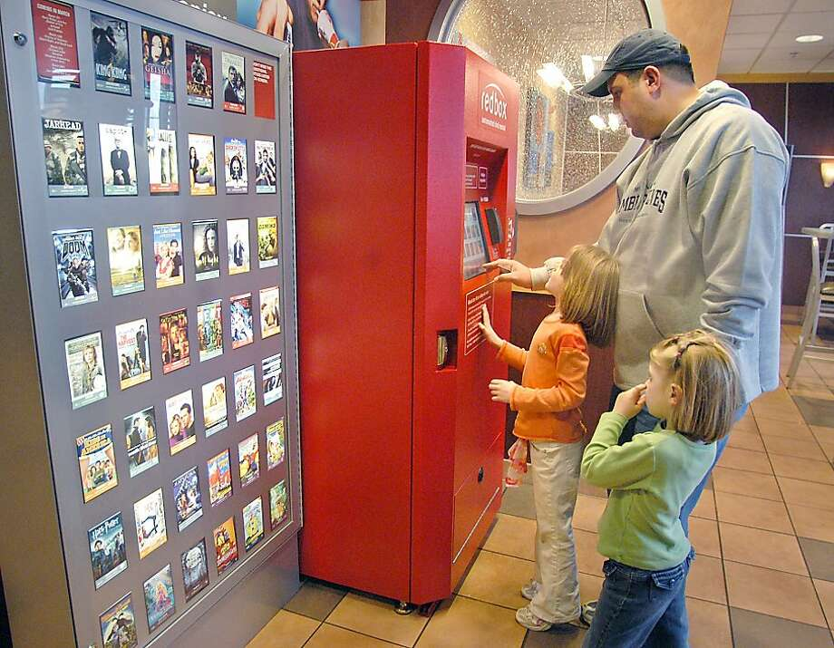 Chris Kliner and his daughters Olivia, 5, right, and Annaliese, 4, select a rental DVD from a Redbox before heading in to eat at McDonald's in Apple Valley, Minn. on Thursday, March 30, 2006. Visiting from Kenosha, Wisconsin, they appreciated the convenience of not having to sign up just to rent a single movie. (AP Photo/Janet Hostetter) Ran on: 04-26-2006 Photo: Janet Hostetter, AP