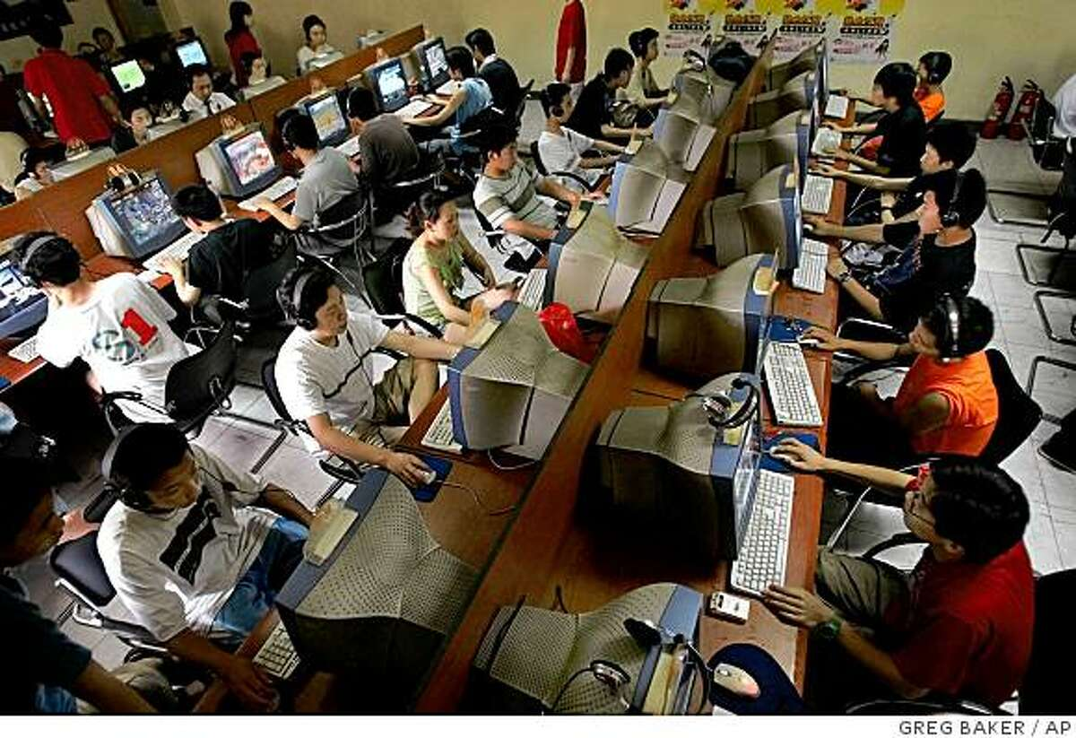 Chinese youth use computers at an Internet cafe in Beijing in this June 18, 2005 file photo. Internet companies that face hearings Wednesday before angry U.S. lawmakers say they can't resist China's effort to censor the Web on their own. But industry analysts say that even if Washington tried to enforce free-speech standards, it is likely to have little effect. (AP Photo/Greg Baker, File)Ran on: 02-15-2006 Chinese youths crowd an Internet cafe in Beijing, where the government controls what they view online. ALSO Ran on: 09-23-2007 Cartoon figures of police provide links on which Internet users can click to report illegal information.