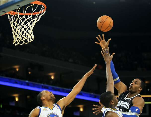 Orlando Magic Dwight Howard takes a shot late into the second half scoring over Golden State Warriors' in their NBA basketball game Thursday, Jan. 12, 2012, in Oakland, Calif. Photo: Lance Iversen, The Chronicle