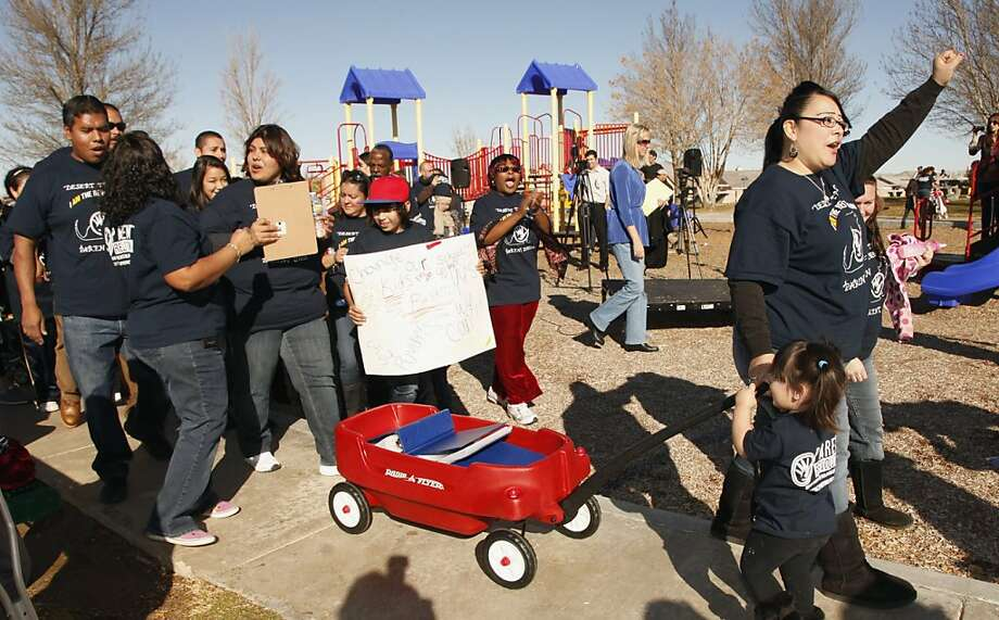 """Parent Olivia Samaripa, right, with her daughter Aria, 2, pull a wagon carrying petitions calling for their school to be converted to a charter school Thursday, Jan. 12, 2012 in the Mojave Desert town of Adelanto, Calif. Parents and guardians at Trails Desert Elementary are filing a petition with the help of Parent Revolution, a Los Angeles-based nonprofit that spearheaded the California's """"parent trigger"""" law to demand reforms. (AP Photo/Damian Dovarganes) Photo: Damian Dovarganes, Associated Press"""