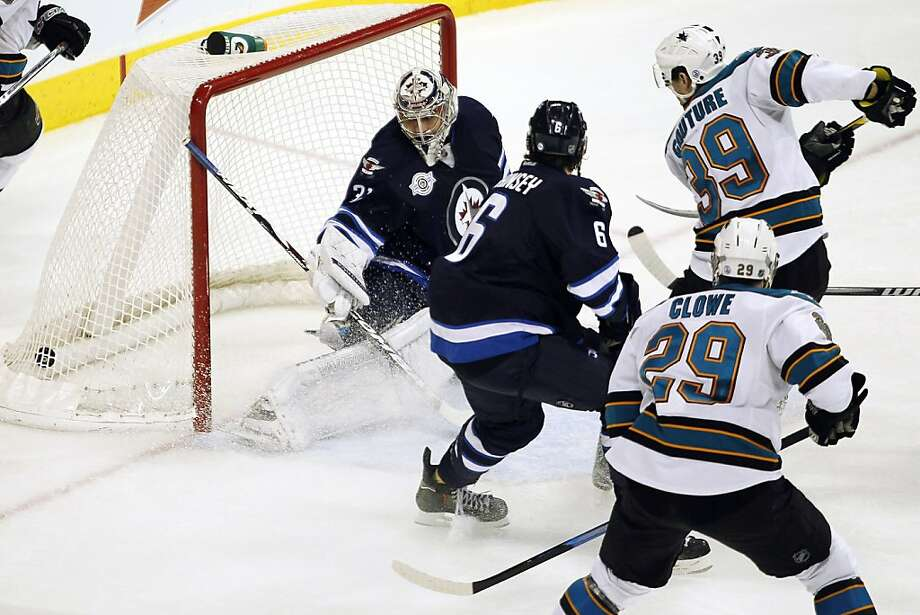 San Jose Sharks' Logan Couture (39) scores against Winnipeg Jets' goaltender Ondrej Pavelec (31) and Ron Hainsey (6) during the second period of an NHL hockey game, Thursday, Jan. 12, 2012, in Winnipeg, Manitoba. (AP Photo/The Canadian Press, John Woods) Photo: John Woods, Associated Press